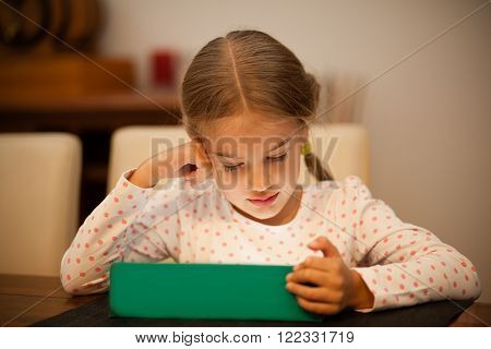 Little girl reading on her tablet at home
