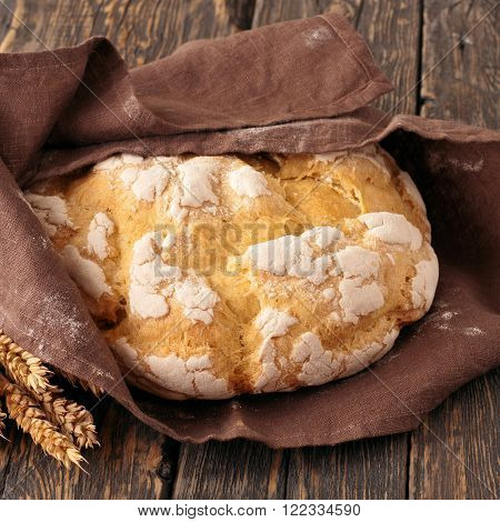 Fresh loaf of homemade bread wrapped in fabric with spikelets of wheat on dark wooden surface closeup. square frame