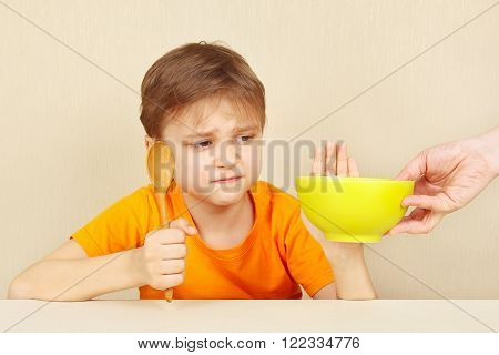 Little cute boy refuses to eat a porridge