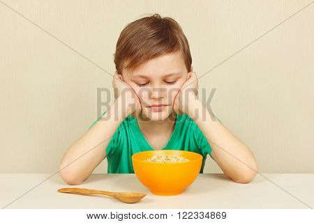 Little displeased boy does not want to eat a porridge