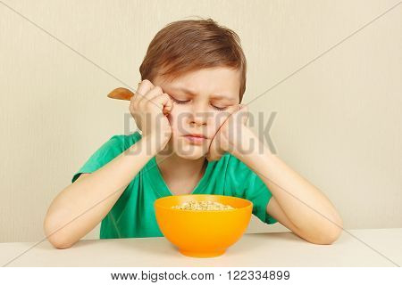 Little discontented boy does not want to eat a cereal