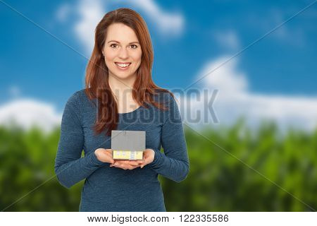 Young smiling woman holding a house with both hands
