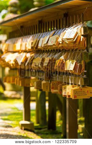 NARA, JAPAN - JUNE 24, 2015: Many small signs or plaques called wooden ema tags carrying written visitor messages and wishes hanging in front of a shinto shrine at the Todai-ji temple complex in Nara Japan. Vertical