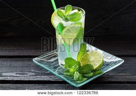 Mojito cocktail with rum, lime, mint and soda in a highball on a glass tray