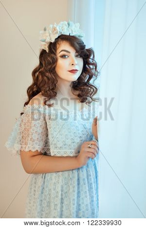 Beautiful young woman standing by a window holding hands curtain. Soft focus with small depth of field.