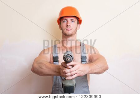 A man in overalls and helmet holding a screwdriver in the two arms