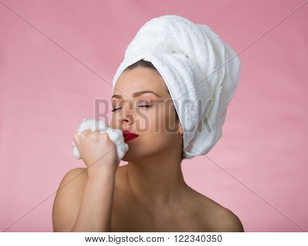Pretty woman with bath towel and soapy sponge