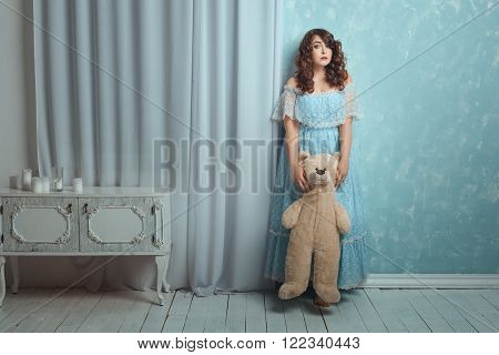 Woman is standing near a wall with a bear toy it is a room for children.