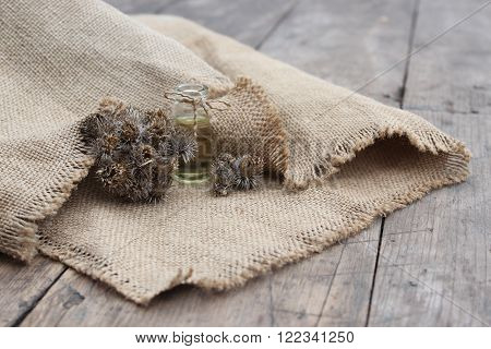 Dry flower and burdock oil jar in the background burlap and wooden planks