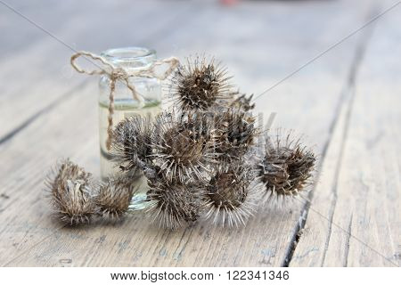 Dry flower and burdock oil jar in the and wooden planks