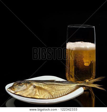 Beer in the glass and fish on a plate, on a black background