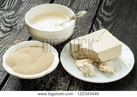 Fresh yeast on paper, instant dry yeast and yeast starter in bowls