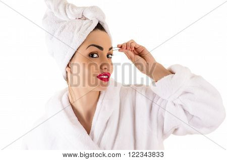 attractive woman in bathrobe plucks eyebrows isolated on white background