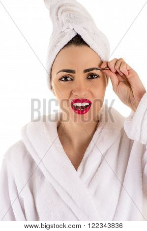 beautiful woman in bathrobe plucks eyebrows isolated on white background
