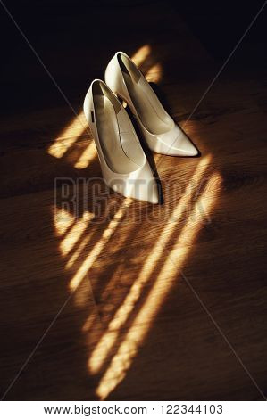 Pair Of Two Elegant, Stylish White Wedding Shoes On Wooden Floor Closeup