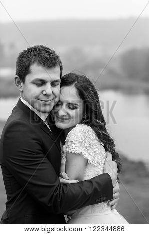 Happy Beautiful Couple Of Newlyweds Hugging Near Romantic Lake Closeup B&w