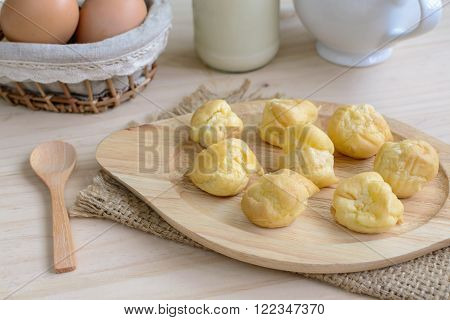Choux pastry cream puffs with milk on wooden table