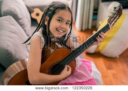 Happy smiling girl, wearing glasses, dreadlocks hair style, learning to play the acoustic guitar
