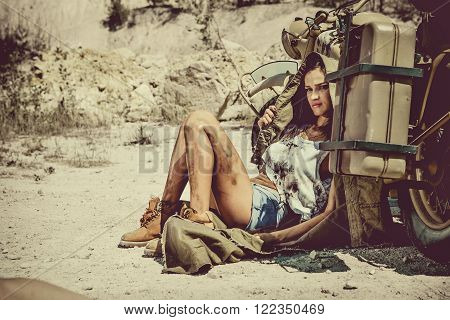 Young sexy woman is relaxing in the shadow of motorbike. Desert on the background.