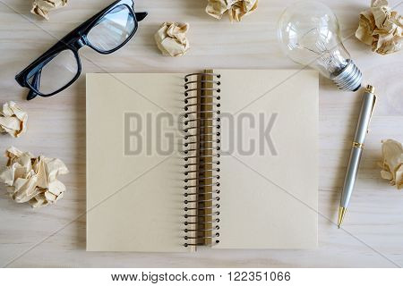 Crumpled paper balls with eye glasses and blank notebook, creative writing concept