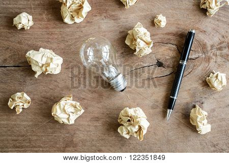 Crumpled paper balls on wooden desk, creative writing concept