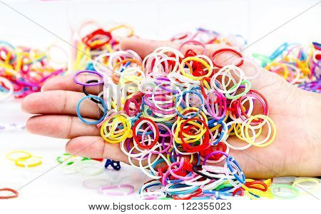 hands and pile of small round colorful rubber bands rainbow color for making rainbow loom bracelets on the table