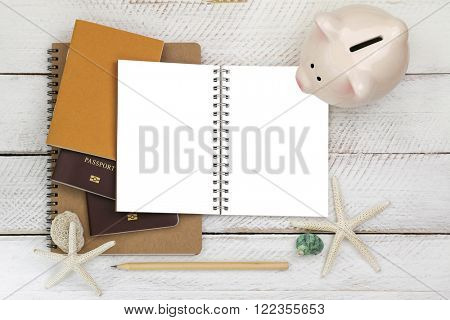 Top view of pink piggybank on blank white notebook with passports and a pencil on wooden background, conceptual idea for planning a trip