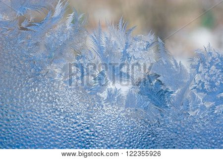 Slightly blurred beautiful frost pattern and drops of water on a window glass (as an abstract winter background)