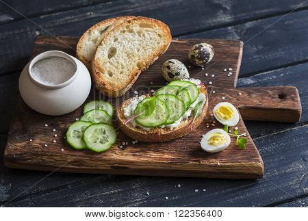 Sandwich with cheese and cucumber and boiled quail eggs - healthy delicious breakfast or snack. On a rustic wooden cutting board
