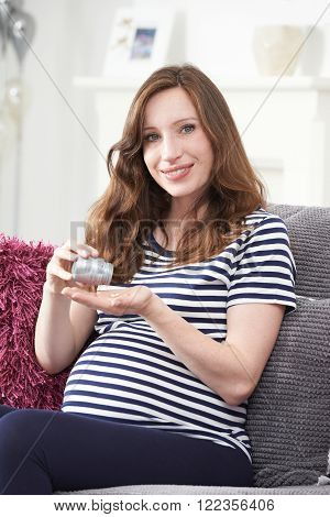 Portrait Of Pregnant Woman Taking Folic Acid Tablets