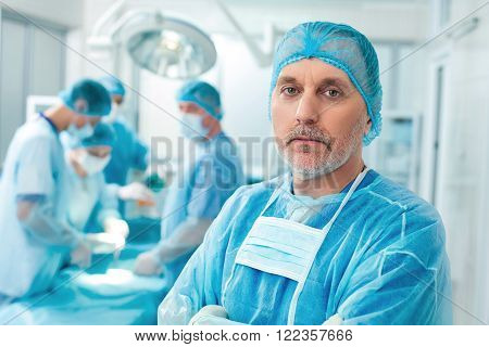 This operation is very serious. Portrait of senior male surgeon standing and looking at camera with seriousness. His colleagues are operating human on background