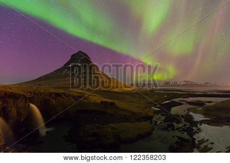 Northern lights moving over Kirkjufell volcano with fully of stars in sky, Iceland natural landscape