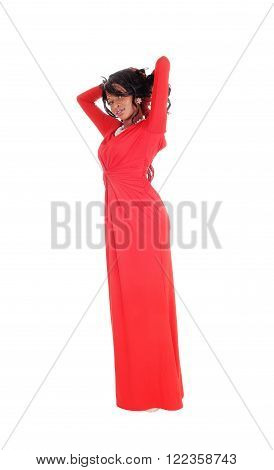 A lovely slim African American woman in a long red dress and curly long black hair standing in profile isolated for white background.