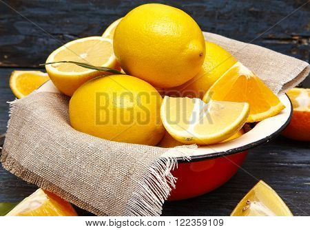 Fresh lemons and oranges in an old plate with linen napkin
