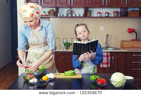 little girl is teaching her mother to cook in a kitchen with different ingredients