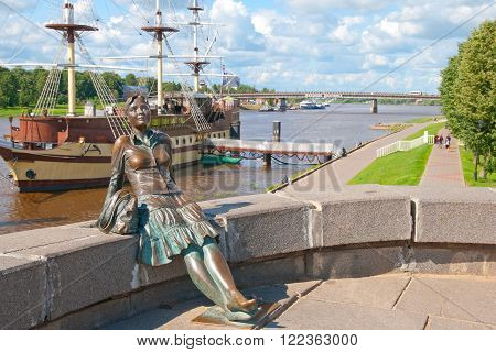 VELIKY NOVGOROD, RUSSIA - JULY 17, 2016. Sculpture of tired tourist girl. On the background is Volkhov River and sailing ship Restaurant Fregat Flagman