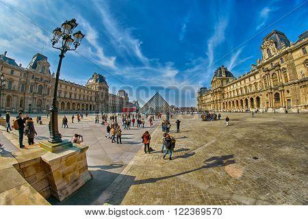 PARIS, FRANCE - 12 MARCH 2016: Tourists walking On Louvre Museum square in Paris