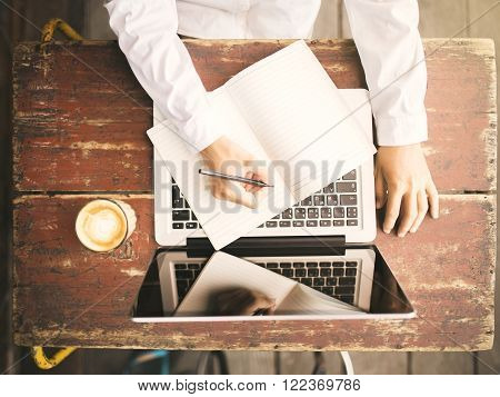 Girl writes in a notebook on a wooden desk with a cup of coffee and laptop