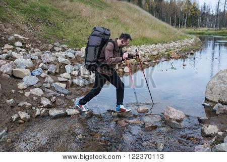Pedestrian tourist crosses the creek on the rocks using trekking poles with a backpack. The man in glasses with bluetooth receiver in the ear.