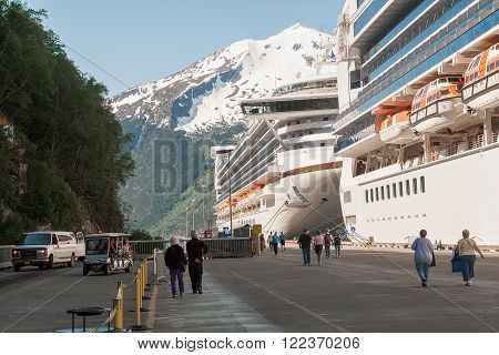SKAGWAY, AK - JUNE 2, 2009: Cruise ships anchored in the port of Skagway Alaska. Passengers walk the main pier to board their ships.
