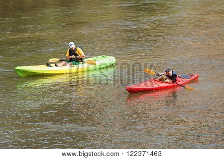 ATLANTA, GA - JULY 2015: A father squirts his son with a water gun while they kayak down the Chattahoochee River on a hot summer day in Atlanta GA on July 25 2015.