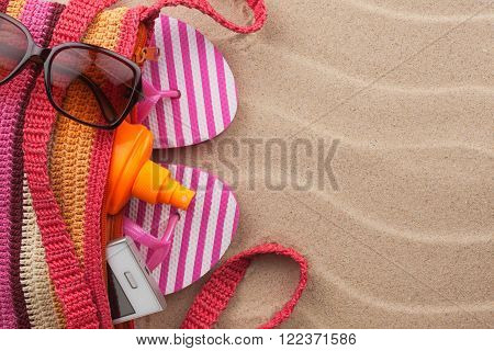 Beach bag with sunscreen flip flops cellphone sunglasses. Summer holiday background