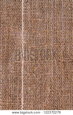 Natural texture of burlap with a white stripe as a background top view