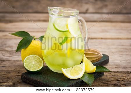 Cold lemonade with ice in the pitcher on the wooden table