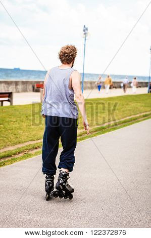 Male Exercise Outdoor On Rollerblades Wearing Sportswear.