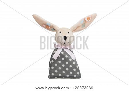 Easter Bunny toy with long ears, with a bow in a gray polka-dot dress on isolated background