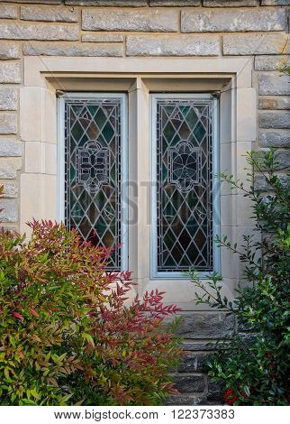 Stained glass window with stone siding and colorful landscaping