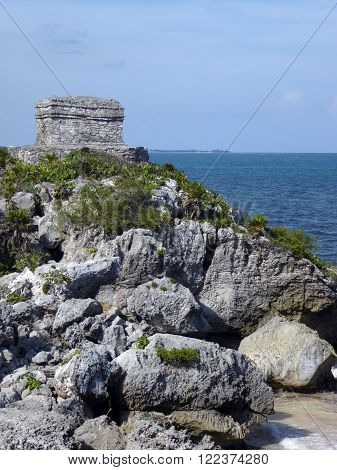 A rocky cliff with a small temple off the Caribbean sea at the Mayan archeological site of Tulum Yucatán Peninsula Mexico.
