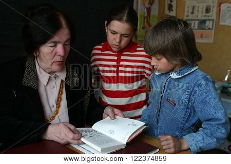 Podol village, Tver region, Russia - May 2, 2006:  Rural teacher reads textbook girls schoolgirls in the classroom primary school.