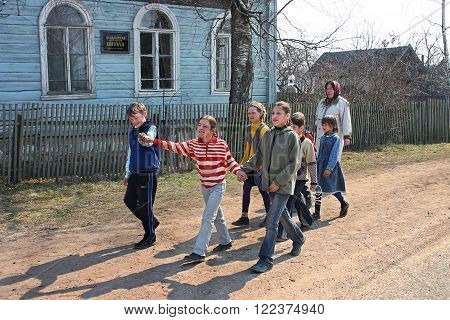 Podol village Tver region Russia - May 2 2006: Pupils of of rural primary school walk in front of the school holding hands.